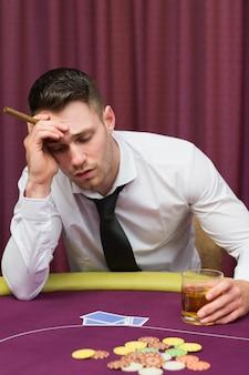 Homem, inclinar-se, pôquer, tabela, segurando, charuto