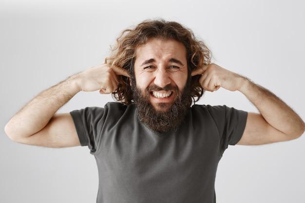 Homem incomodado do oriente médio fechava os ouvidos e fazia caretas devido ao barulho alto e perturbador