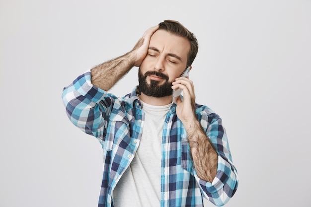 Homem incomodado e chateado ouve más notícias enquanto fala ao telefone