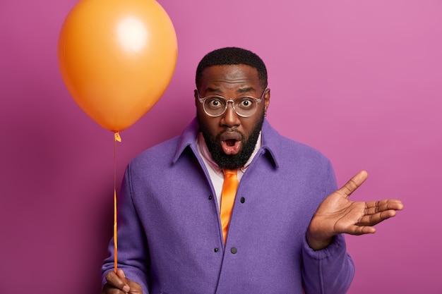 Homem inconsciente chocado sem saber onde a festa é realizada, levanta a palma da mão com hesitação, segura um balão de ar laranja, encara com olhos esbugalhados e boca aberta