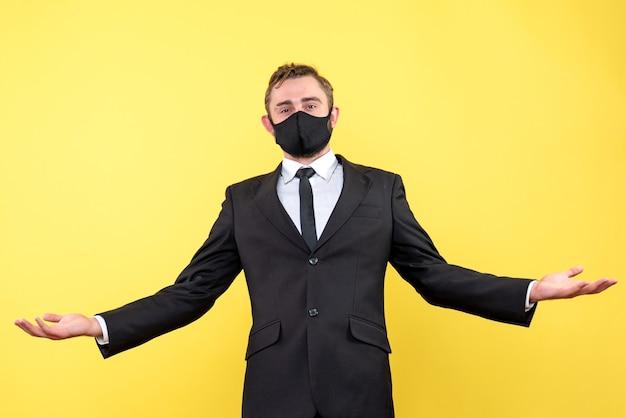 Homem incrível surpreso com máscara facial sobre amarelo isolado