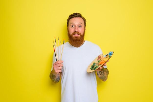 Homem indeciso com barba e tatuagem pronto para desenhar com pincéis
