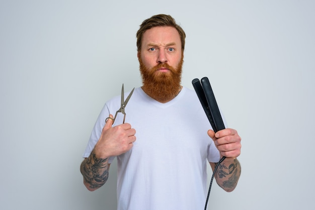 Homem indeciso com tesoura e alisador está pronto para trabalhar com cabelo