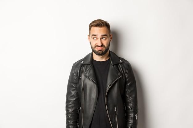 Homem indeciso e melancólico em jaqueta de couro preta, olhando para a esquerda e se sentindo desconfortável, de pé
