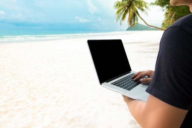 Homem independente, trabalhando com o computador portátil on-line na praia