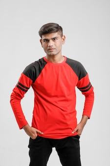 Homem indiano / asiático em camiseta vermelha e mostrando expressão múltipla sobre branco