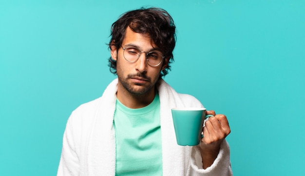 Homem indiano bonito adulto vestindo roupão de banho e tomando um café