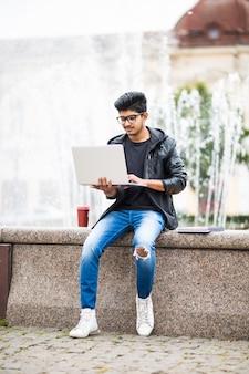 Homem indiano bonito com laptop enquanto está sentado perto da fonte no centro da cidade em um dia