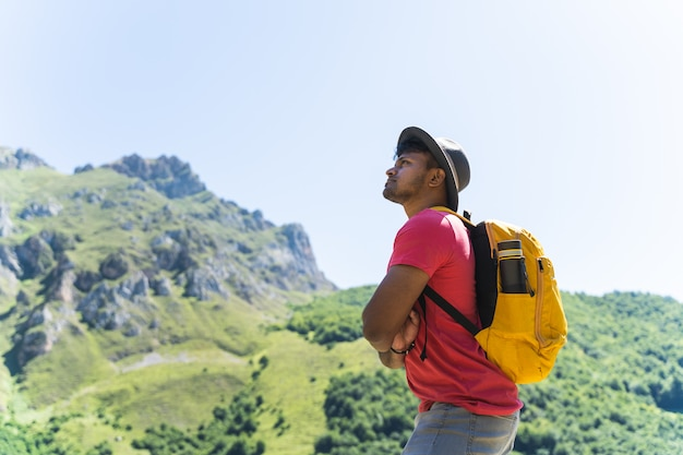 Homem indiano carregando uma mochila amarela, olhando para a montanha