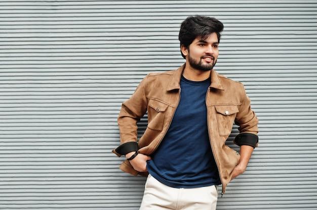 Homem indiano casual elegante usa camiseta azul e jaqueta marrom posando contra uma parede cinza.