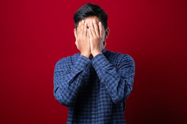 Homem indiano com bigode, camisa casual com expressão triste, cobrindo o rosto com as mãos enquanto chora. conceito de depressão sobre fundo vermelho
