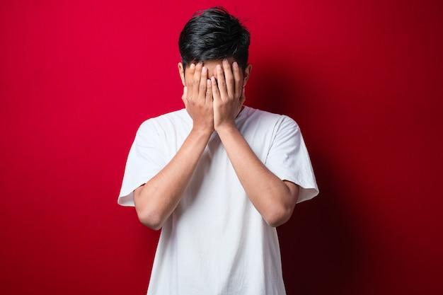 Homem indiano com bigode, camiseta branca casual com expressão triste, cobrindo o rosto com as mãos enquanto chora. conceito de depressão sobre fundo vermelho