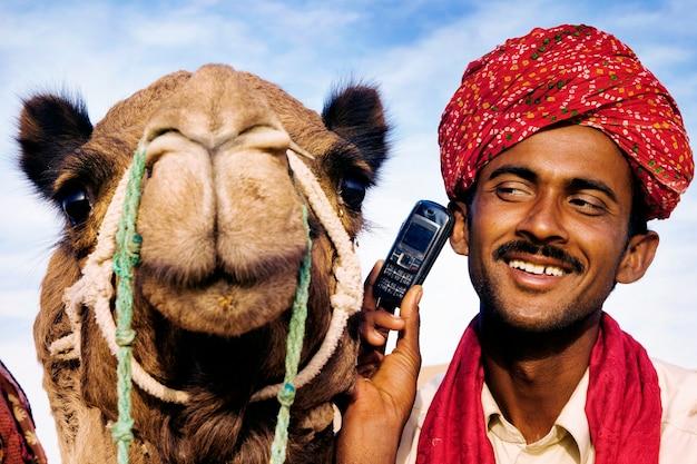 Homem indiano com camelo falando ao telefone