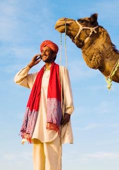 Homem indiano com camelo fazendo uma chamada