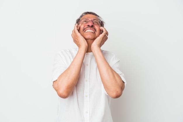 Homem indiano de meia idade, isolado no fundo branco, chorando e chorando desconsoladamente.