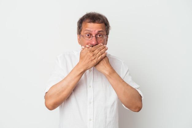 Homem indiano de meia idade isolado no fundo branco, cobrindo a boca com as mãos parecendo preocupado.