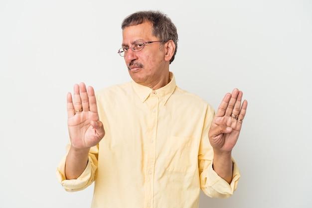 Homem indiano de meia idade, isolado no fundo branco, de pé com a mão estendida, mostrando o sinal de stop, impedindo-o.