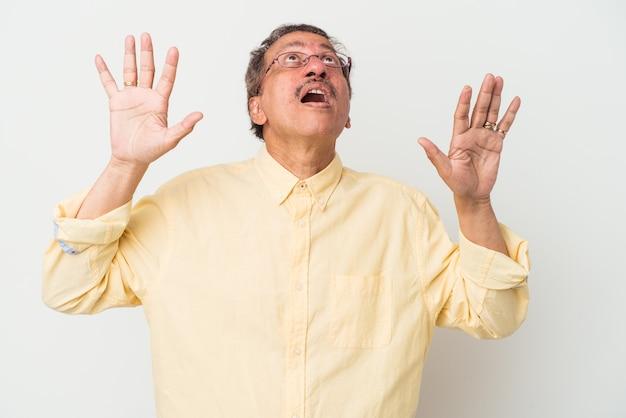 Homem indiano de meia idade isolado no fundo branco, gritando para o céu, olhando para cima, frustrado.