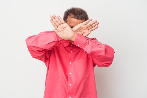 Homem indiano de meia idade isolado no fundo branco, mantendo os dois braços cruzados, conceito de negação.
