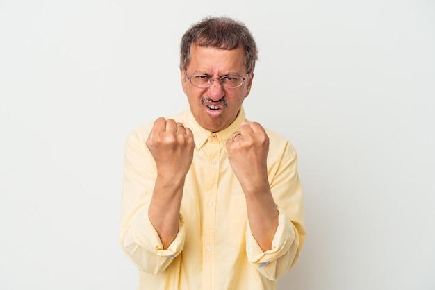 Homem indiano de meia idade isolado no fundo branco, mostrando o punho para a câmera, expressão facial agressiva.