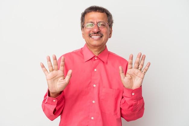 Homem indiano de meia idade isolado no fundo branco, rejeitando alguém que mostra um gesto de nojo.