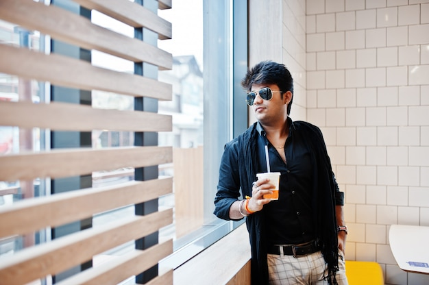 Homem indiano elegante em óculos de sol fica perto da janela com uma xícara de café no café de fast-food.