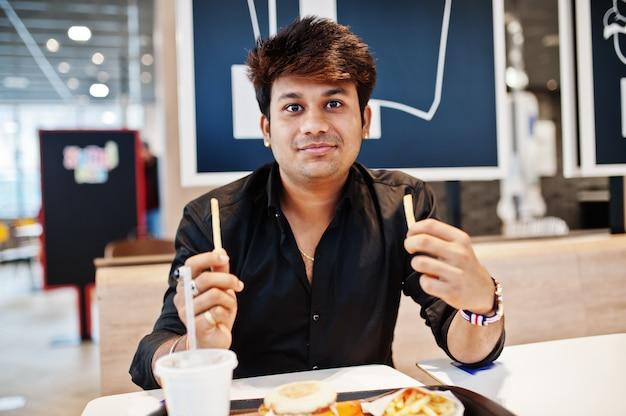 Homem indiano elegante sentado no café de fast-food e comendo batatas fritas.