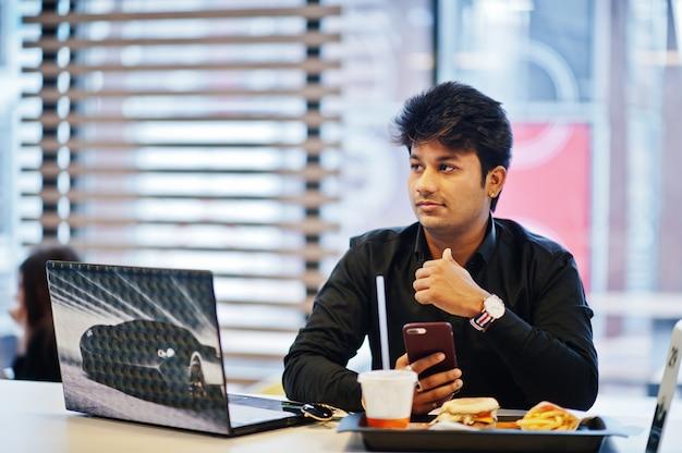 Homem indiano elegante sentado no café fast-food contra seu laptop com o celular na mão.