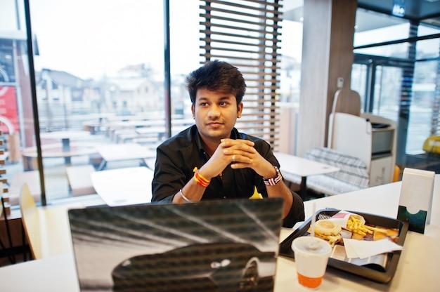 Homem indiano elegante sentado no café fast-food contra seu laptop.