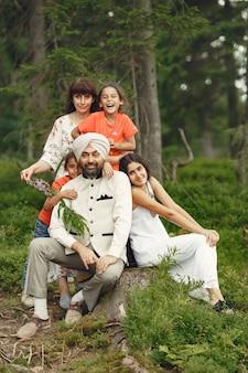 Homem indiano em uma floresta. macho em um turbante tradicional. família internacional em uma floresta de verão.