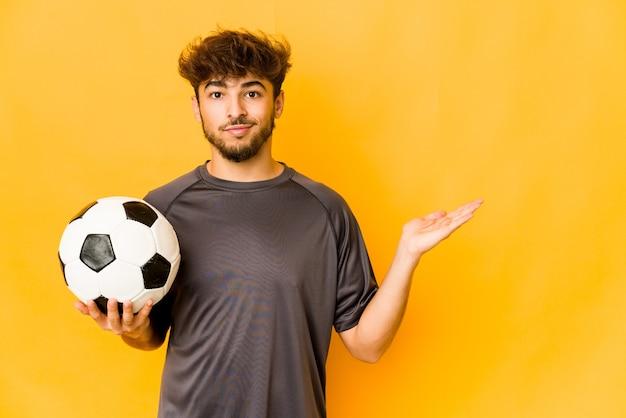 Homem indiano jovem jogador de futebol mostrando um espaço de cópia na palma da mão e segurando a outra mão na cintura.