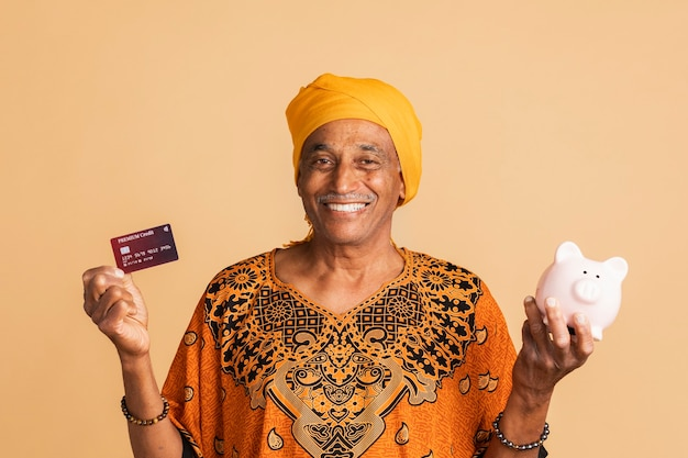 Homem indiano misto feliz com um cartão de crédito e um cofrinho