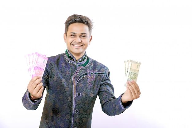 Homem indiano mostrando nota de moeda indiana