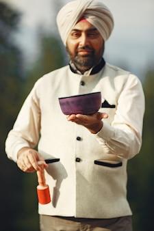 Homem indiano nas montanhas. macho em um turbante tradicional. hinduísta com coisas especiais para rituais.
