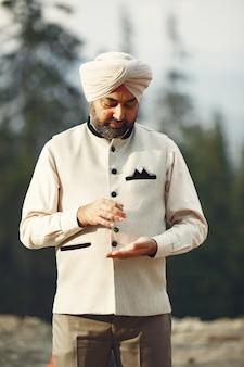 Homem indiano nas montanhas. macho em um turbante tradicional. hinduísta com mascote.
