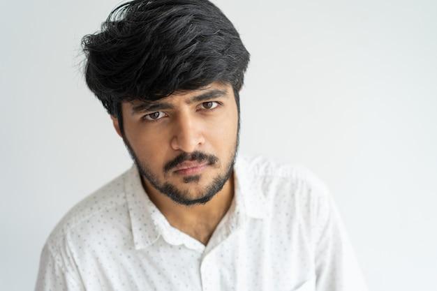 Homem indiano novo brutal resistente com a barba que olha a câmera.