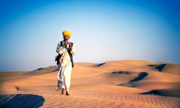 Homem indiano que joga a tubulação de vento em um deserto.