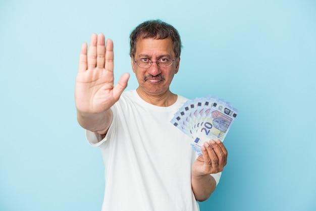 Homem indiano sênior segurando projeto de lei isolado em um fundo azul em pé com a mão estendida, mostrando o sinal de pare, impedindo-o.