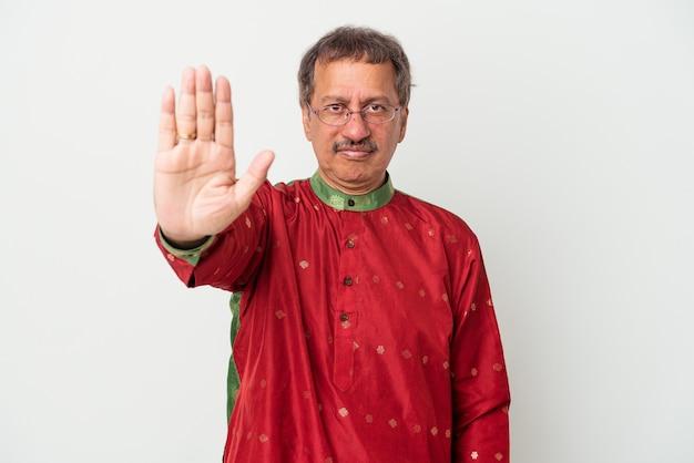 Homem indiano sênior vestindo um traje indiano, isolado no fundo branco, de pé com a mão estendida, mostrando o sinal de pare, impedindo-o.