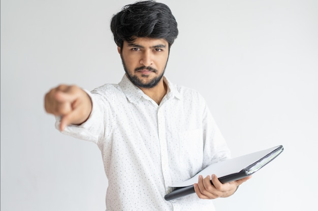 Homem indiano sério apontando para você e segurando documentos