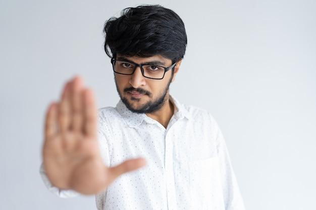 Homem indiano sério mostrando a palma da mão aberta ou parar o gesto e olhando para a câmera.