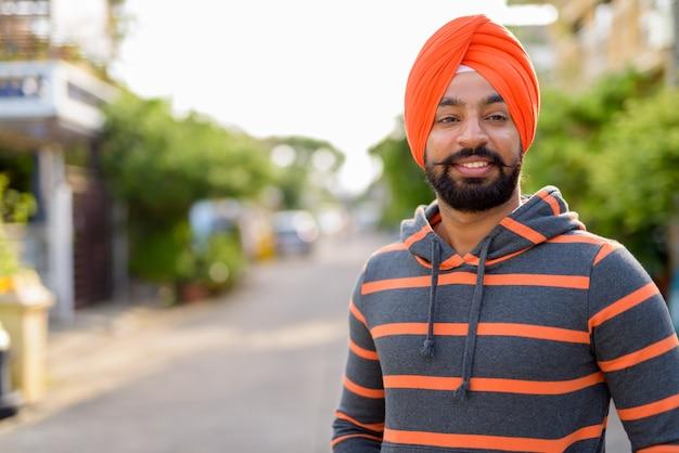 Homem indiano sikh feliz sorrindo ao ar livre e usando turbante laranja