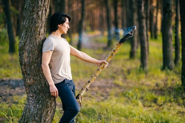 Homem indígena indiano do redskin do nativo americano que está acima da árvore na floresta com queima, vara de madeira de fumo. rito xamã. cerimônia mística. invocação de espírito de fogo. reserva antiga.