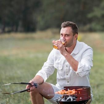 Homem indo ao churrasco ao ar livre e bebendo cerveja