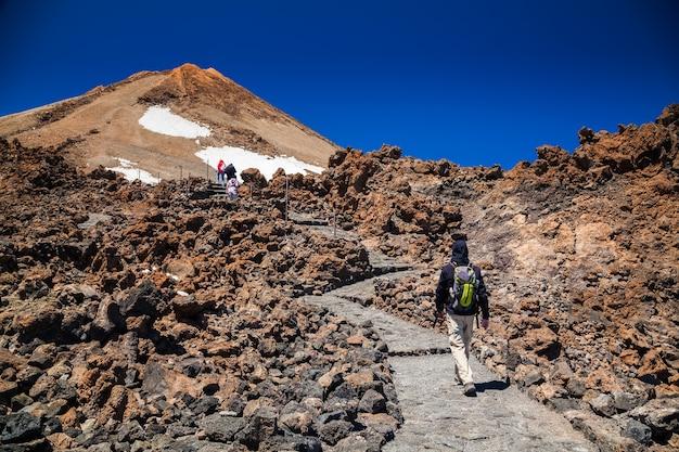Homem indo ao topo do vulcão teide em tenerife, ilhas canárias, espanha