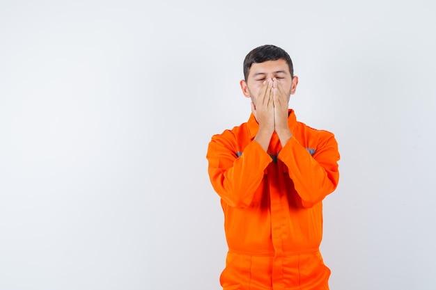 Homem industrial apertando as mãos no rosto de uniforme e parecendo esperançoso. vista frontal.