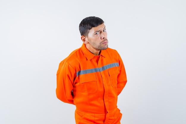 Homem industrial com as mãos atrás das costas de uniforme e parecendo duvidoso, vista frontal.