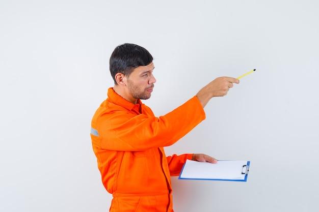 Homem industrial dando instruções, segurando um lápis, prancheta de uniforme.