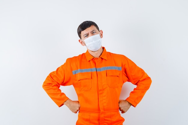 Homem industrial de mãos dadas na cintura em uniforme, máscara e olhando pensativo. vista frontal.