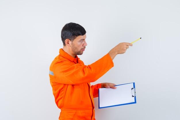 Homem industrial de uniforme dando instruções, segurando o lápis, a prancheta.